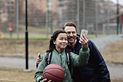 Smiling son taking selfie with father after basketball practice in winter - p426m2101471 by Maskot
