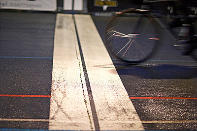 Close up of cyclist racing over finishing line at velodrome - p429m928888f by Dark Horse