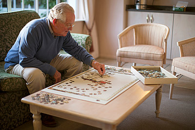 Older man on sofa solving jigsaw puzzle - p555m1305743 by Resolution Productions