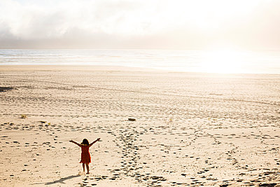 Caucasian girl standing with arms outstretched on beach - p555m1411259 by Adam Hester