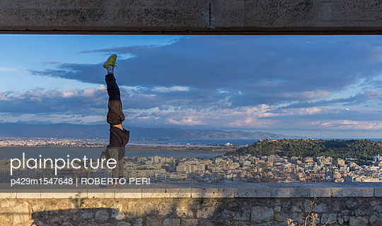 plainpicture | Photo library for authentic images - plainpicture p429m1547648 - Man doing handstand on wall... - plainpicture/Cultura/ROBERTO PERI