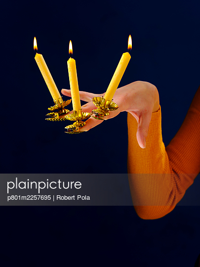 Woman with three candlesticks and candles on her fingers - p801m2257695 by Robert Pola