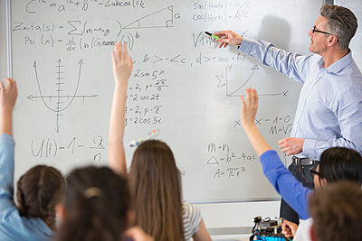 Male teacher leading physics lesson at whiteboard in classroom - p1023m1506420 by Martin Barraud