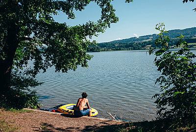 Junger Mann mit Schlauchboot am See - p1085m1042857 von David Carreno Hansen
