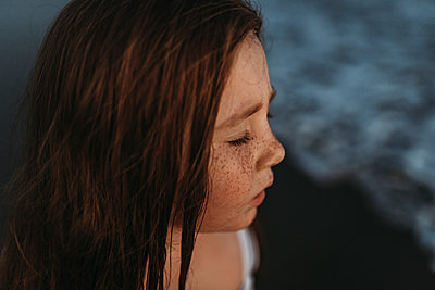 Portrait of cute red headed girl with freckles closing eyes in ocean - p1166m2136533 by Cavan Images