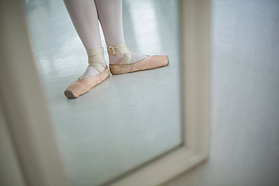 Reflection of ballerinas feet wearing ballet shoes - p1315m1230712 by Wavebreak