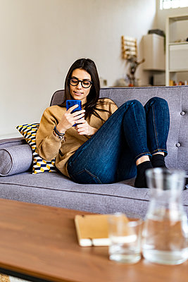 Woman wearing eyeglasses using mobile phone while sitting on sofa at home - p300m2251991 by Giorgio Fochesato