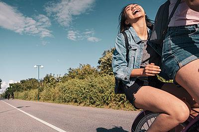 Teenage girl laughing while sitting on bicycle behind female friend on street - p426m2270781 by Kentaroo Tryman