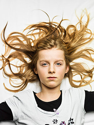 Portrait of teenage girl lying down with long blonde hair - p429m802295 by Cultura