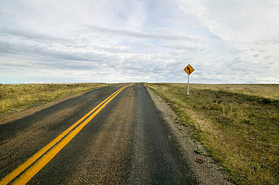 An empty highway with a sign indicating a curve up ahead; Saskatchewan, Canada - p442m837705f by Benjamin Rondel