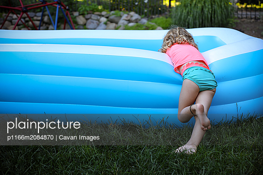 girl with blowup pool - p1166m2084870 by Cavan Images