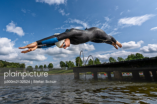 Young female triathlete jumping into a lake - p300m2132524 by Stefan Schurr
