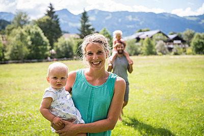 Junge Familie mit zwei Töchtern auf Wiese - p1142m2109454 von Runar Lind