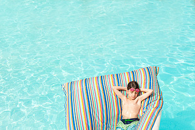 High angle view of boy lying on inflatable raft in swimming pool - p1166m1186690 by Cavan Images