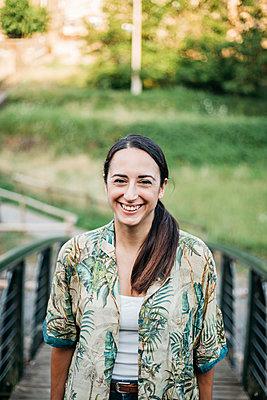 Smiling woman standing over footbridge in public park - p300m2207085 by Xavier Lorenzo