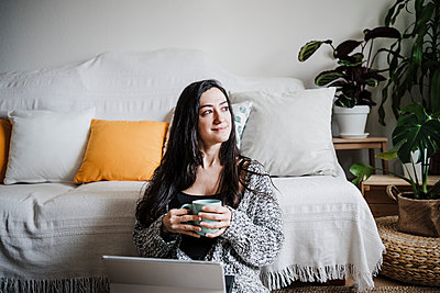 Smiling woman with laptop holding coffee cup while sitting on floor against sofa in living room - p300m2264981 by Eva Blanco