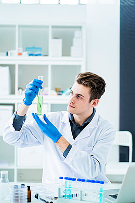 Male scientist holding graduated cylinder at laboratory - p300m2265369 by Giorgio Fochesato