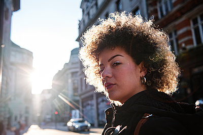 Curly haired woman during sunny day in city - p300m2273659 by Angel Santana Garcia