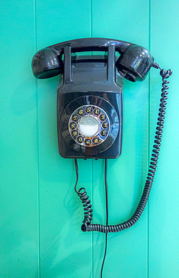 Dial phone mounted on green wall - p429m2058413 by Seb Oliver