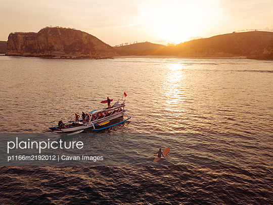 Aerial view of surfers and boat in the ocean, Lombok, Indonesia - p1166m2192012 by Cavan Images