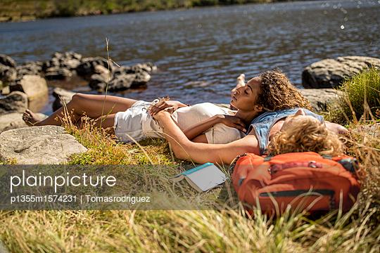 Junges Paar macht eine Pause beim Wandern - p1355m1574231 von Tomasrodriguez