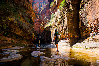 Side view of woman standing in stream amidst rocky mountain - p1166m1194038 by Cavan Images