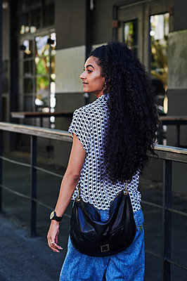 Black-haired woman in casual outfit in the city - p1640m2246164 by Holly & John