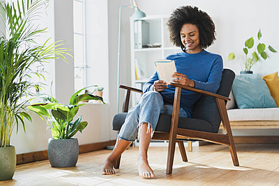 Smiling woman reading book while sitting on armchair at home - p300m2276422 by Steve Brookland