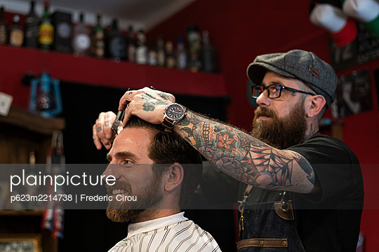 Hairdresser cutting man's hair in salon - p623m2214738 by Frederic Cirou