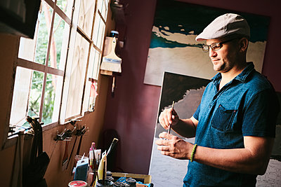 Mid adult male Cuban artist mixing paint with brush in his workshop - p1166m2078303 by Cavan Images