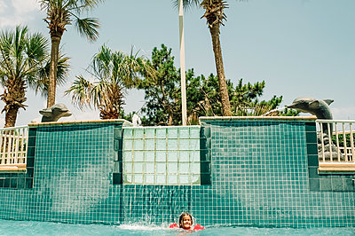 Portrait of happy girl enjoying water fountain in swimming pool - p1166m2094918 by Cavan Images