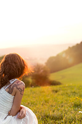 Germany, Baden-Wuerttemberg, Black Forest, back view of woman on Alpine meadow watching sunrise - p300m1081304f by Miriam Dörr
