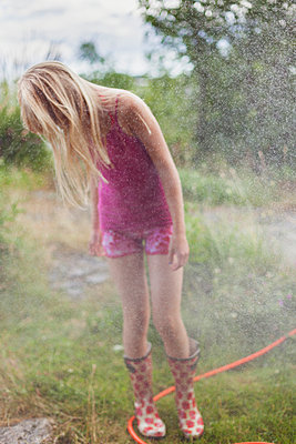 Girl With Long Hair Standing In A Sprinkler In The Garden - p847m888797 by Bildhuset
