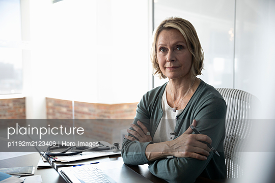 Mature female doctor sitting at desk with arms folded - p1192m2123409 by Hero Images