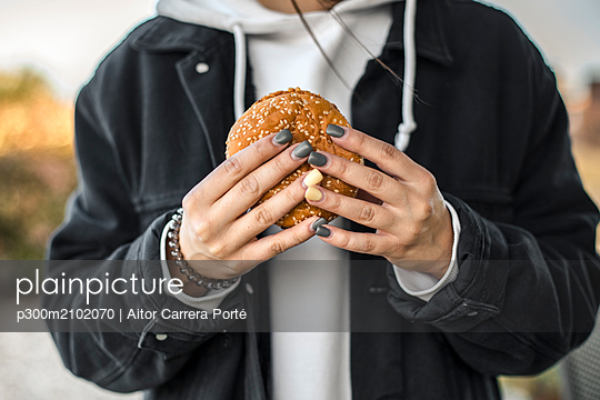 Hands of young woman with painted nails holding a hamburger, close-up - p300m2102070 by Aitor Carrera Porté
