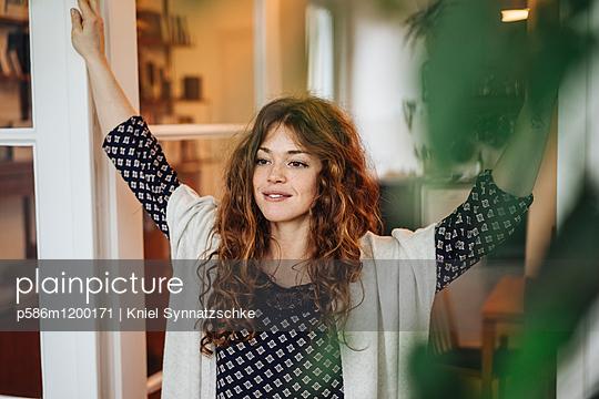 Junge Frau mit roten Haaren beim Tagträumen - p586m1200171 von Kniel Synnatzschke