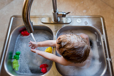 High angle view of boy playing with water in sink - p1166m1210621 by Cavan Images