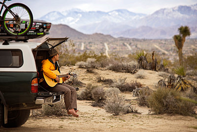Man playing guitar while sitting on car trunk - p1166m1406823 by Cavan Images