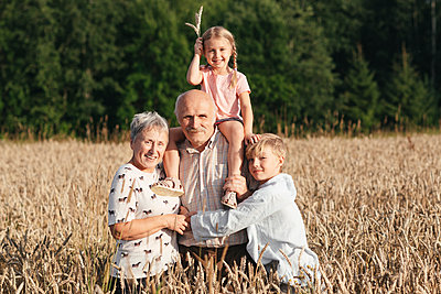 Family portrait of grandparents with their grandchildren in an oat field - p300m2143871 by Ekaterina Yakunina