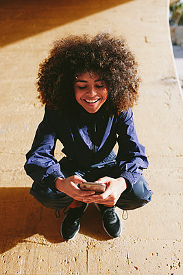 Stylish young woman wearing tracksuit and using cell phone outdoors - p300m2179963 by Lightsy Studio