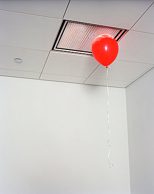 Red balloon in office - p3721917 by James Godman