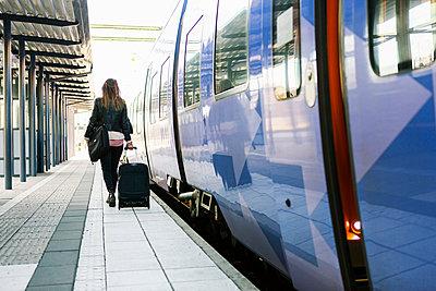 Rear view of businesswoman pulling wheeled luggage on railroad station platform - p426m1085549f by Kentaroo Tryman