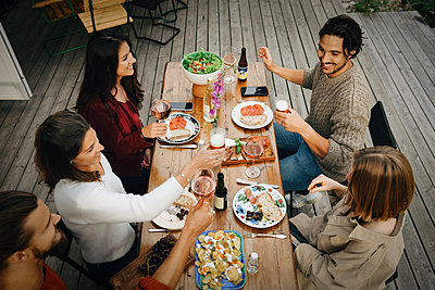 High angle view of friends enjoying drinks while having food during garden party - p426m2149270 by Maskot