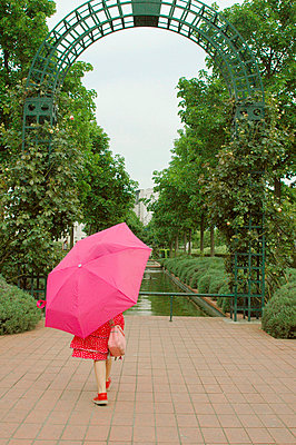 Girl under a large pink umbrella - p6810045 by Sandrine Léon