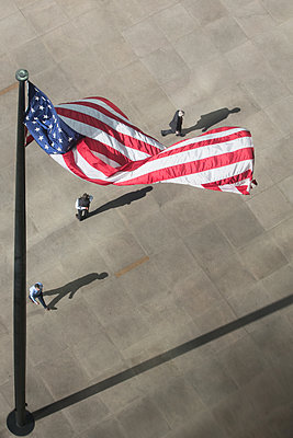 USA flag and pedestrians in New York City - p919m1355156 by Beowulf Sheehan