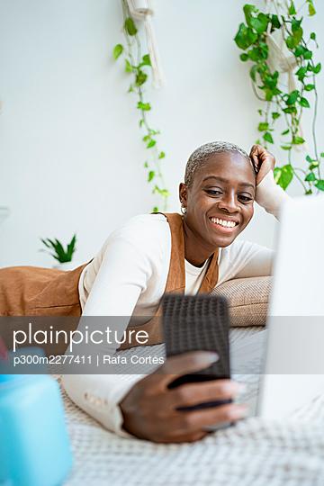 Happy female entrepreneur taking selfie through smart phone at home - p300m2277411 by Rafa Cortés