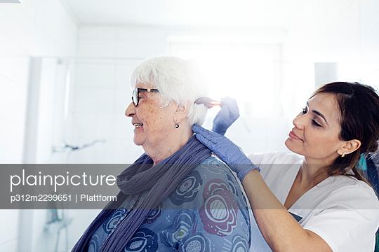 Nurse combing woman's hair in bathroom - p312m2299651 by Plattform