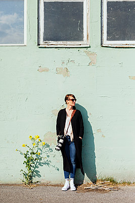 Female photographer leaning on wall - p1185m1080893f by Astrakan