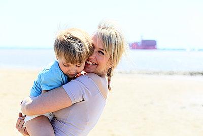Mutter mit Sohn am Strand - p1258m1573233 von Peter Hamel