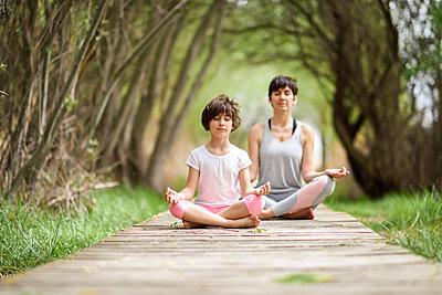 Mother and daughter doing yoga on boardwalk - p300m1587704 von Javier Sánchez Mingorance